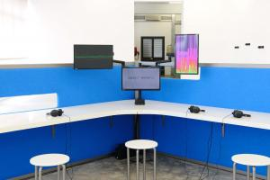 The Whole Truth, 2012, Reverse engineered lie detector, 3 channel video, stereo sound, desk, 3 chairs, 3 artificial plants, 24 minutes, 612 x 435 x 190 cm, Ed.5 + 2 AP